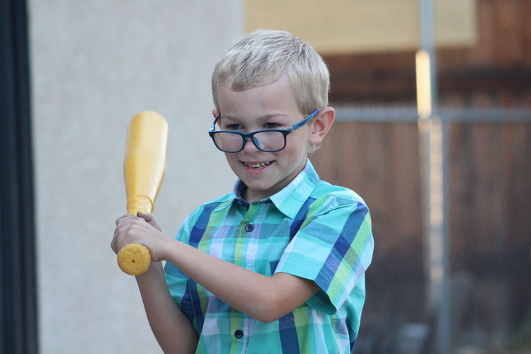 Cute smiling boy holding baseball bat while standing outdoors