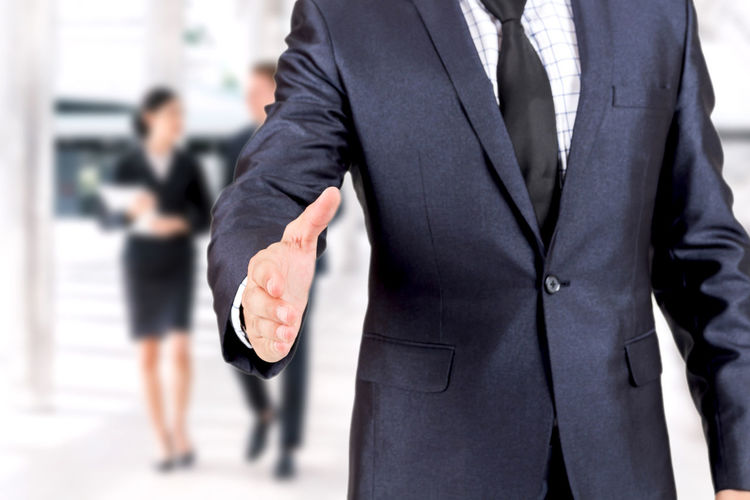 Midsection of businessman gesturing in office
