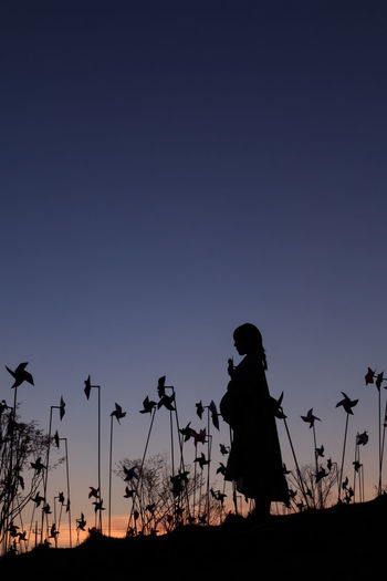 Silhouette pregnant woman standing by pinwheel toys on field during sunset