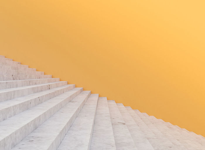 Minimal concrete staircase and yellow wall , 3d rendering