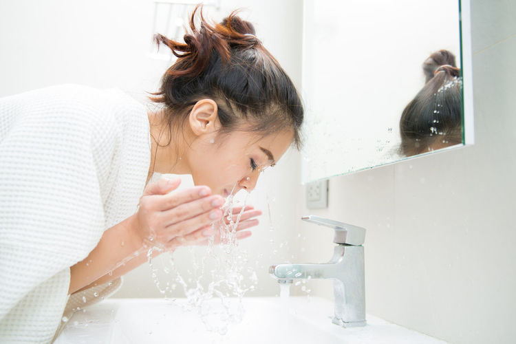 Bathroom Domestic Bathroom Domestic Life Domestic Room Faucet Hairstyle Headshot Home Hygiene Indoors  Lifestyles One Person Portrait Real People Running Water Sink Water Women Young Adult Young Women