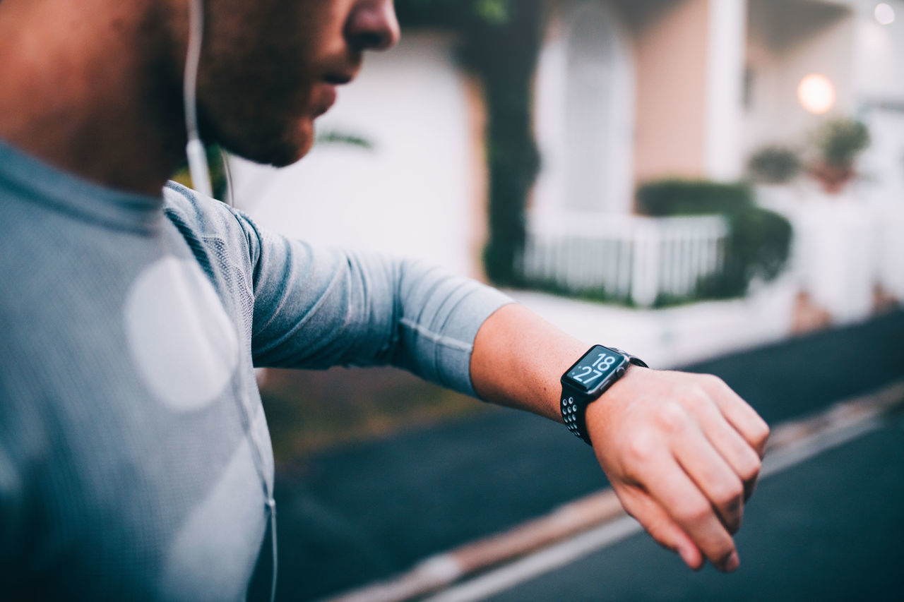 Close-up of man with wristwatch against street