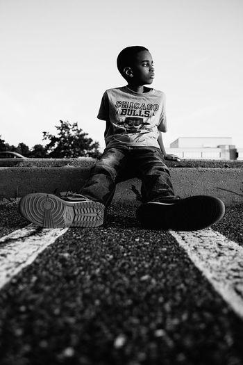 Full length of boy sitting against clear sky