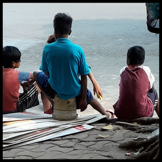 Rear view of people sitting on shore