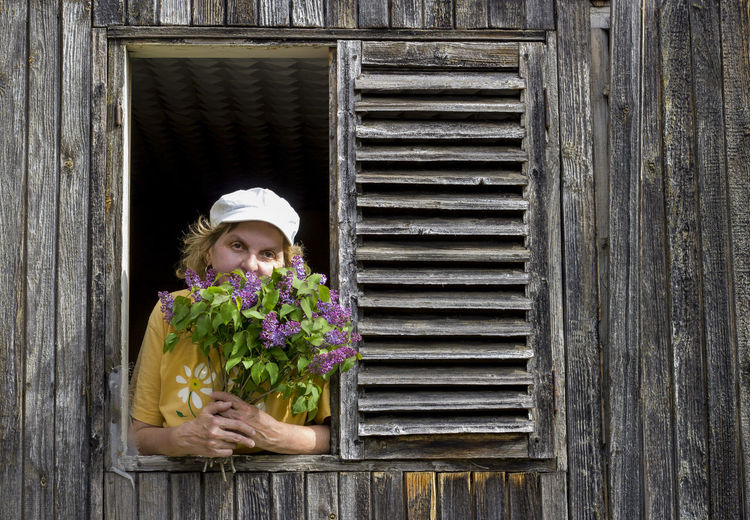 Portrait of woman with pink flowers on window