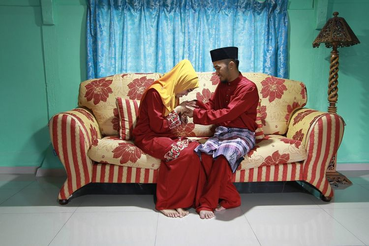 Full length of couple shaking hands while sitting on sofa at home