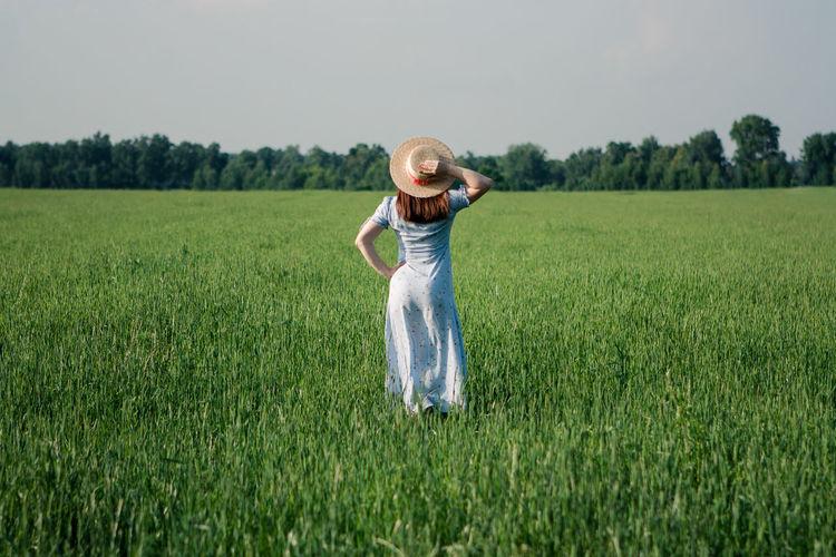 Woman in sunhat in green field