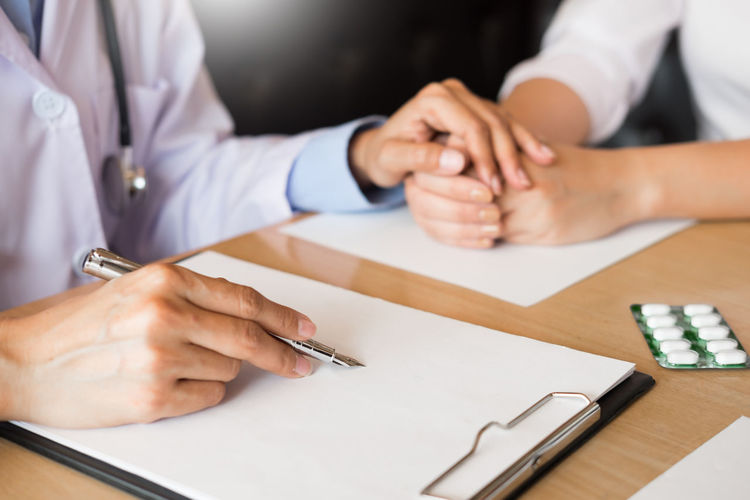 Adult Business Close-up Communication Coworker Finger Hand Holding Human Body Part Human Hand Indoors  Men Midsection Occupation Office Paper Pen People Real People Table Two People Women