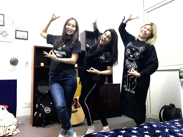 Dorm room fun. Multicultural. China Multiculturalism International Studies Young Adult Friendship Full Length Young Women People Happiness Adult Arts Culture And Entertainment Indoors  Looking At Camera Casual Clothing