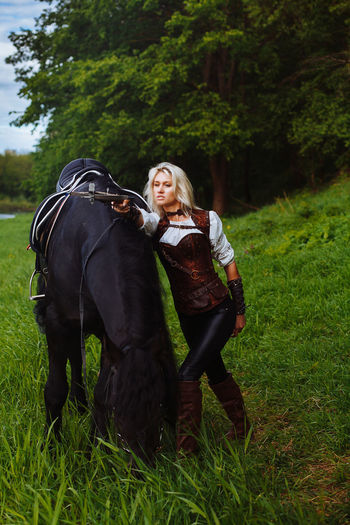 Young Woman With Horse On Grassy Field