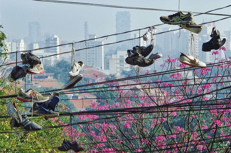 Low Angle View Of Shoes Tied On Ropes Against City