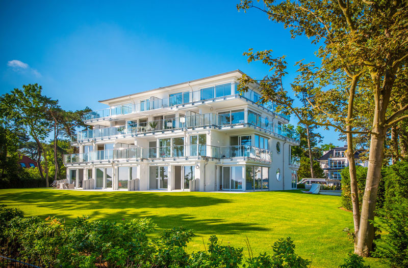 white apartment house Building Exterior Architecture Built Structure Plant Grass Tree Building Sky Nature Blue Residential District House Green Color Day Lawn No People Modern Outdoors Luxury Clear Sky