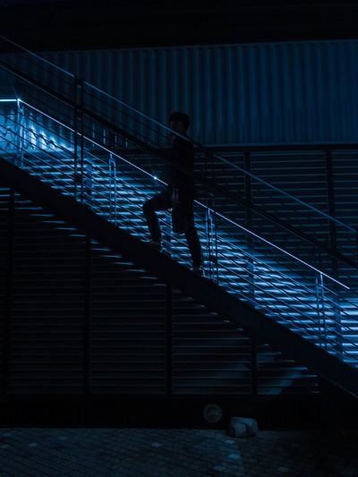 Silhouette man walking on staircase at night