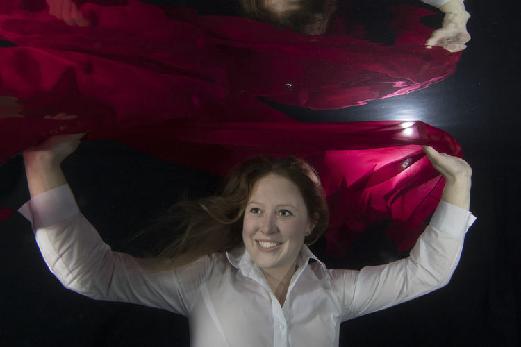 Smiling Young Woman Holding Red Scarf In Underwater