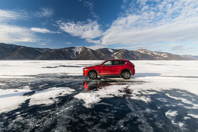 Red car on snowcapped mountains against sky