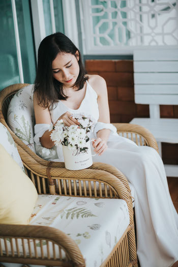 Woman Holding Flower While Sitting On Chair