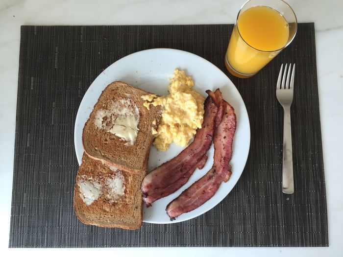 High Angle View Of Breakfast Served In Plate By Orange Juice On Place Mat