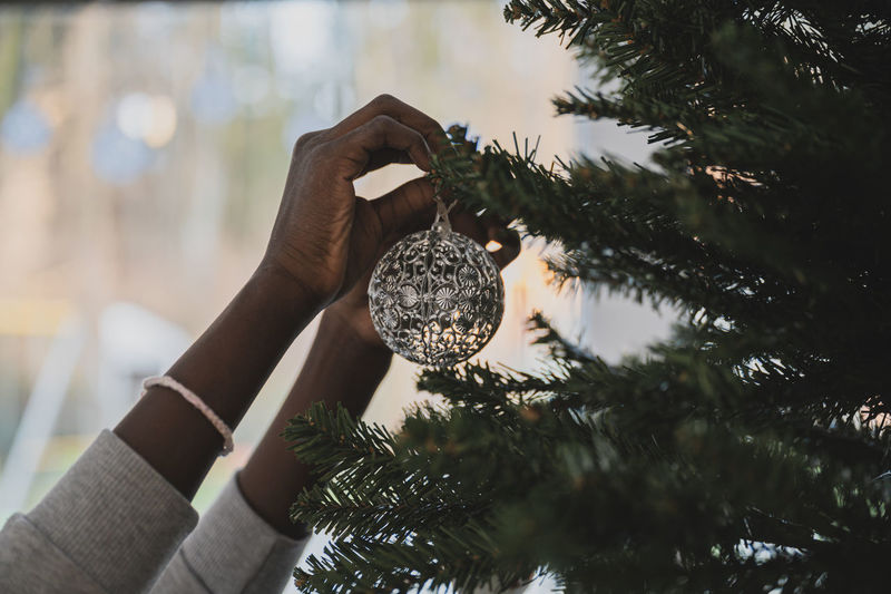 Cropped hands of woman decorating christmas tree