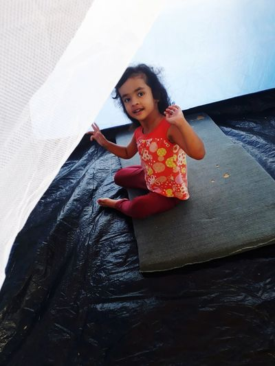 Portrait of cute girl sitting in tent