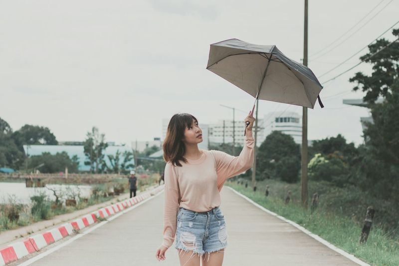 Young Woman Holding Umbrella On Road Against Sky
