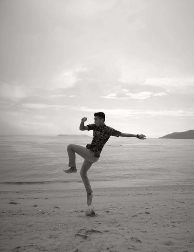 Full length of man jumping at beach against sky