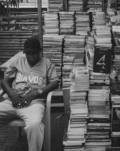 Full length of man sitting on books