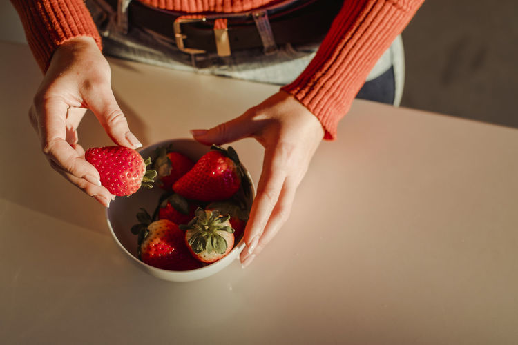 Midsection of woman holding strawberry