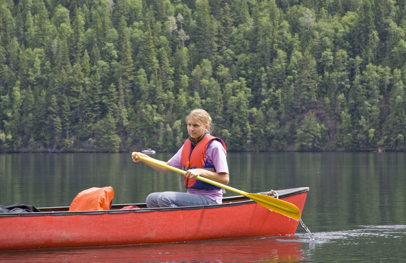 Young Woman Looking Away While Canoeing On Lake