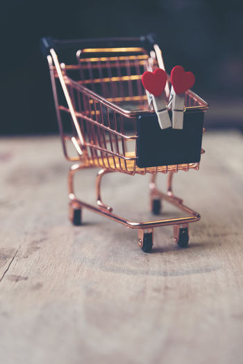 Close-up of clothespins with shopping cart on table against black background
