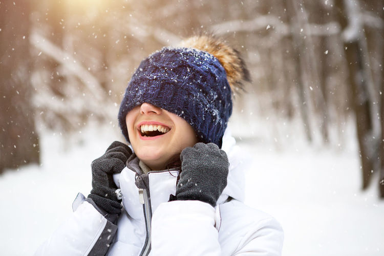 A woman with a warm knitted hat pulled over her eyes smiles and enjoys the snow, the spring