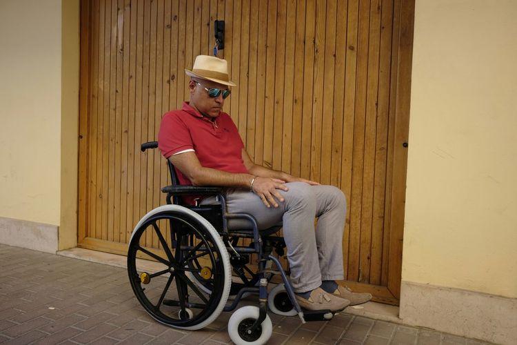 Man sitting on wheelchair on footpath