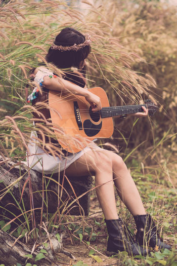 Musical Instrument Music Guitar Playing String Instrument Land Musical Equipment One Person Real People Leisure Activity Arts Culture And Entertainment Nature Field Plant Sitting Holding Acoustic Guitar Musical Instrument String Plucking An Instrument Lifestyles Skill  Musician Outdoors