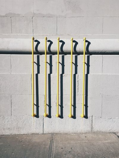 Yellow painted pipes on wall