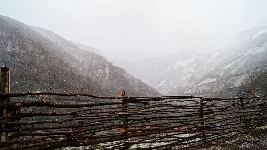 Snow covered landscape against sky during rainy season
