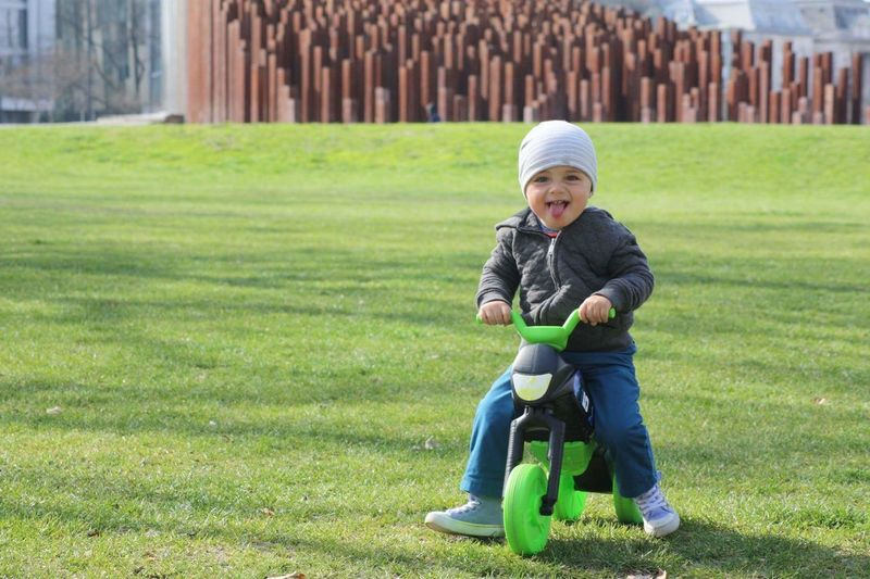 Portrait Of Baby Boy Riding Tricycle On Grassy Field