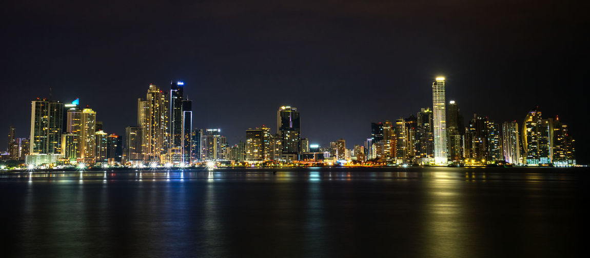 Illuminated buildings by sea against sky at night, skyline of panama