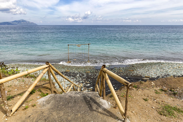 Bamboo steps leading down to a swing at Blue Stone Beach near Ende, Indonesia. ASIA Batu Ende INDONESIA Indonesian Rural Tourist Travel Trip Adventure Attraction Beach Biru Destination East Nusa Tenggara Flores Outdoor Pengajawa Pentai Savu Sea Southeast Stone Tourism Vacation