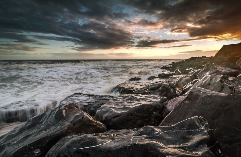 Rocks in sea against cloudy sky during sunset