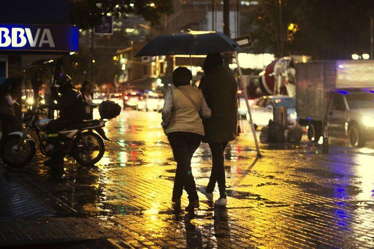 People Walking On Wet Street At Night