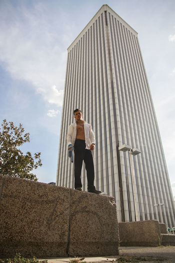 Man with fully unbuttoned shirt standing against modern building in city