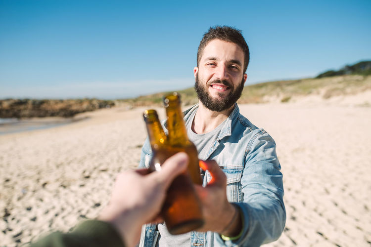 Smiling young man toasting alcoholic drink bottle with friend at beach during sunny day