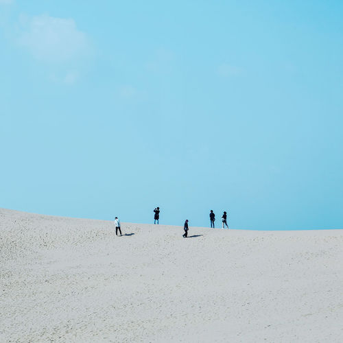 Low angle view of men standing on sand dunes against sky