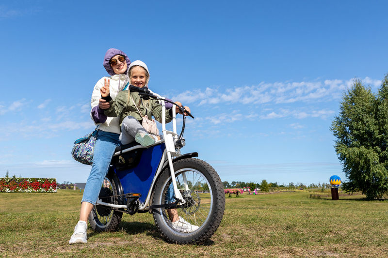 Woman riding motorcycle on field against sky
