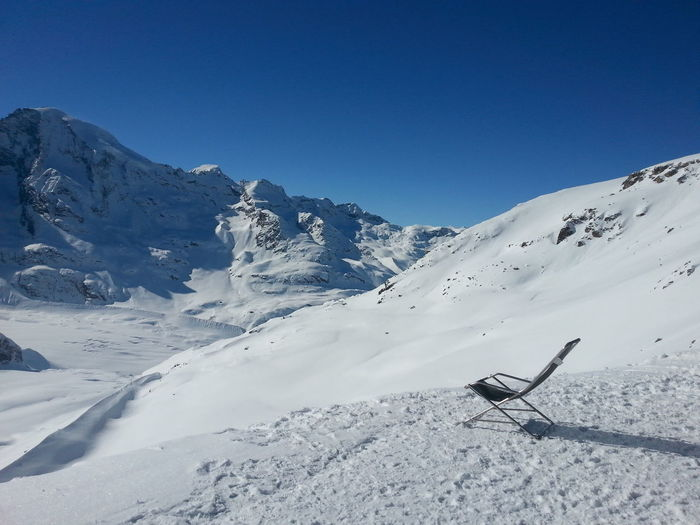 Empty foldable chair on snow covered landscape against clear blue sky