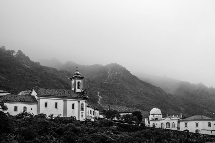 Low angle view of buildings and mountain against sky in foggy weather
