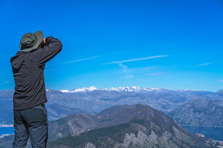 Rear view of man standing against mountain and sky