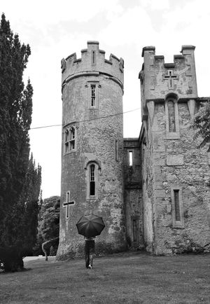 By the castle History Architecture Bnwphotography Bnw_city Bnw_of_our_world Bnw_photography Outdoors Castle Tower Castello Umbrellas Umbrella☂☂ Umbrella Revolution By The Castle Blackandwhite Photography Girl With Umbrella Old Castle Howth Ireland