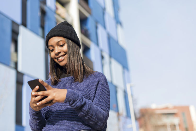 Low angle view young woman using phone while standing against building
