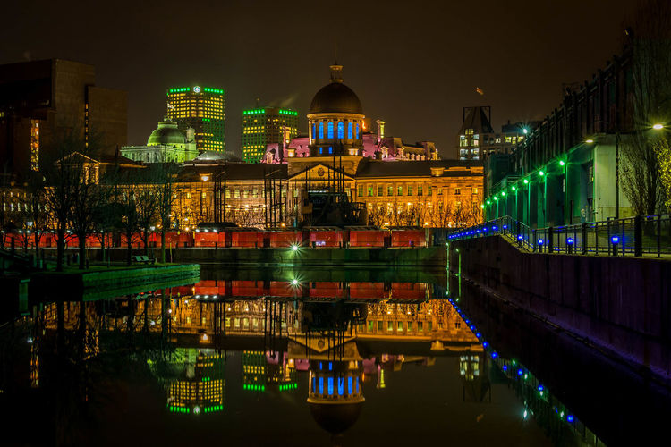Illuminated bonsecours market reflection in sea against sky at night