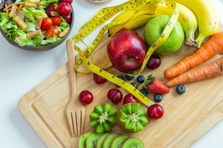 Close-up of fruits and vegetables with tape measure on cutting board